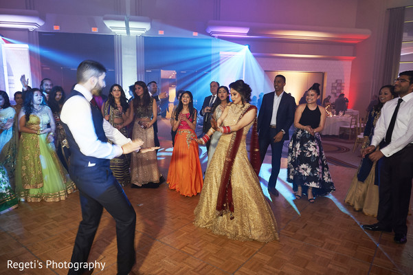 Indian bride and her groom dancing during the reception party.