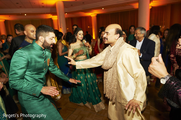 Indian groom dancing with relatives.