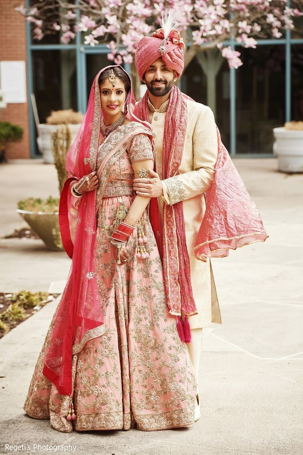 Maharani in pink saree with her groom wearing a pink turban.