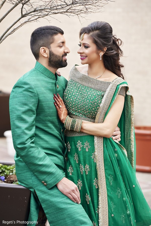 Indian couple in green attires during photo session.