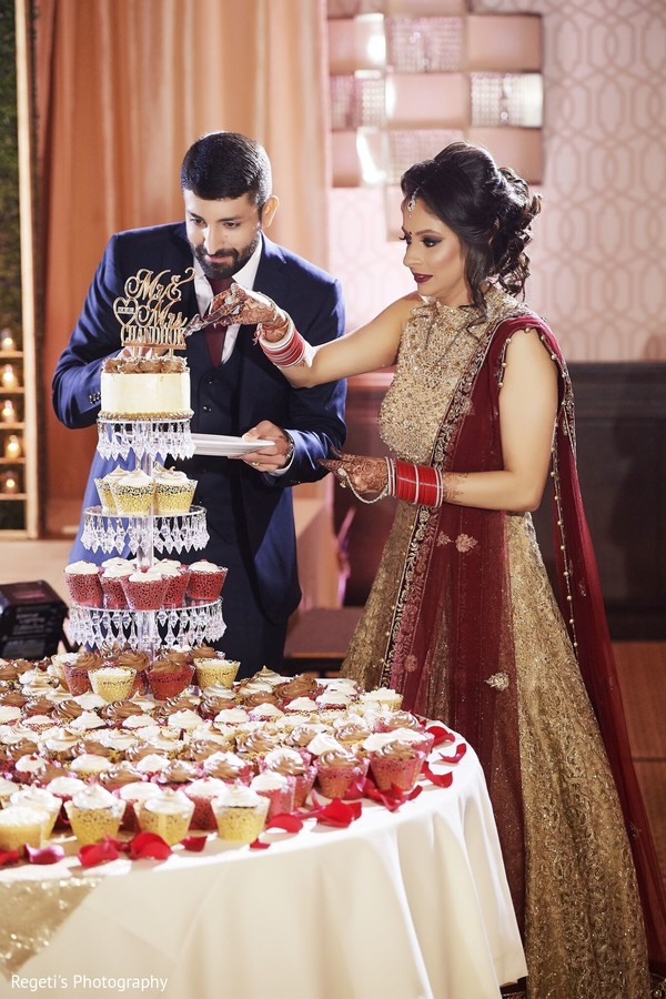 Maharani in golden lengha cutting the cake with her groom.