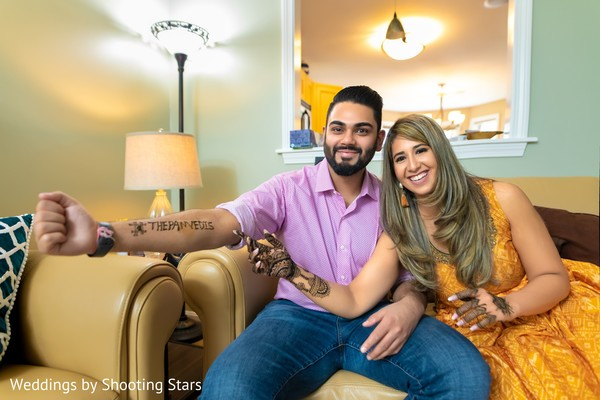 Indian couple showing off their henna stained arms
