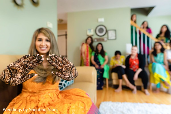 Indian bride showing off her mehndi with her Indian family