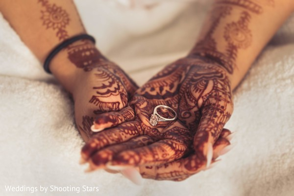 Maharani's henna stained hands holding her engagement ring