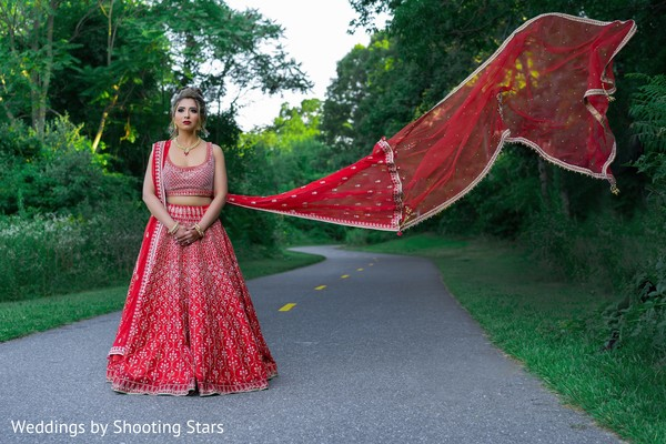 Indian bride posing with her cape billowing in the wind