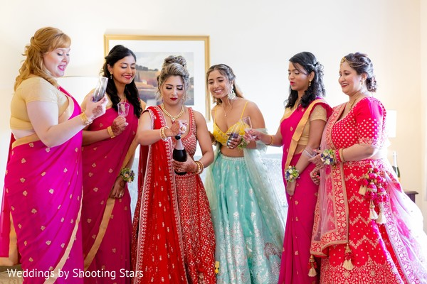 Indian bride and Indian bridesmaids opening a bottle