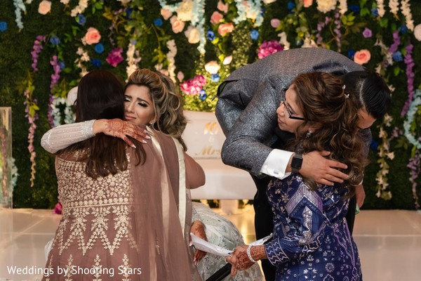 Indian groom and Indian bride hugging their Indian relatives