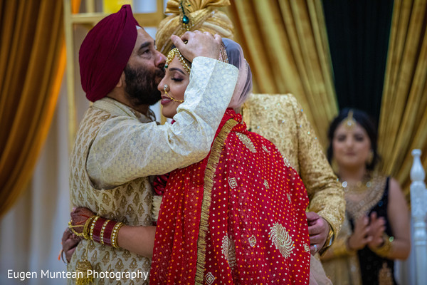 Indian bride kissed by father.