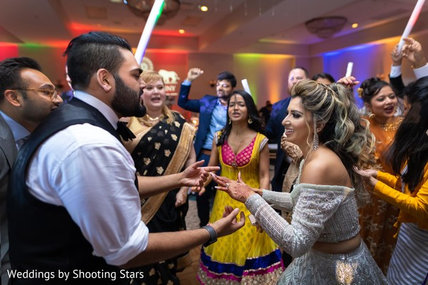 Indian newlyweds dancing in the middle of their Indian relatives