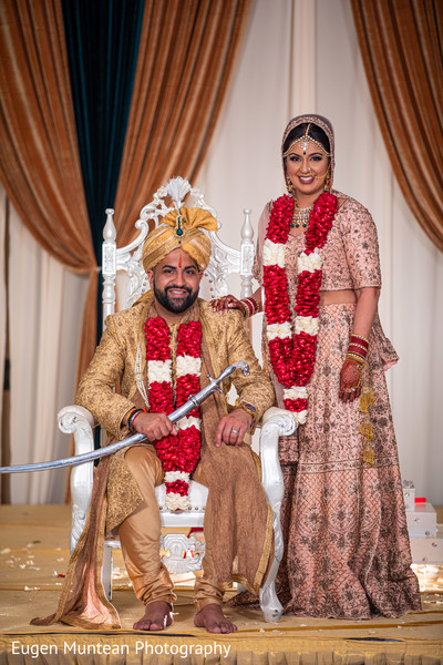 Indian groom with bride posing with ceremony outfits.
