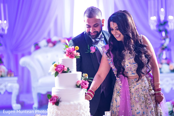 Indian Bride and Groom at the reception with wedding cake