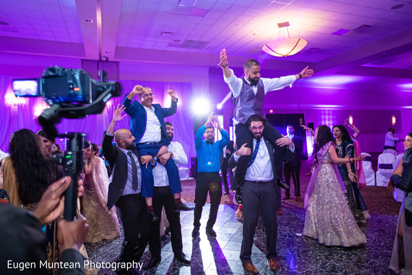 Indian guests and groom dancing at reception celebration