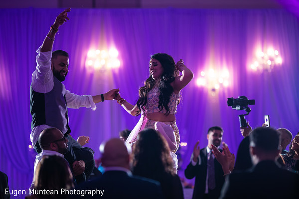 Indian couple being lifted at wedding reception celebration