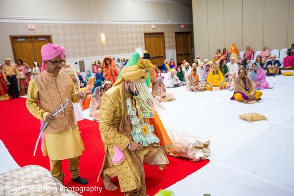 Indian groom making reverence at sikh ceremony altar.