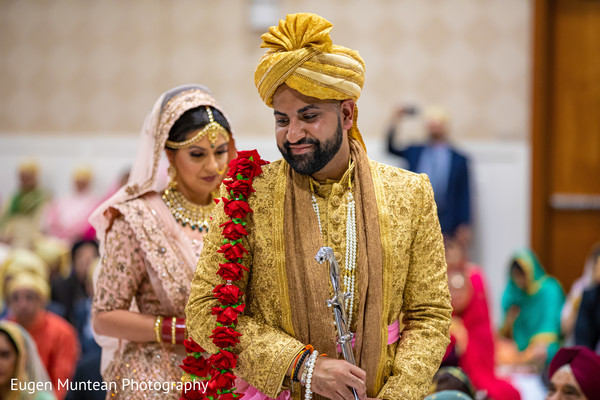 Indian groom with red roses garland on shoulder.