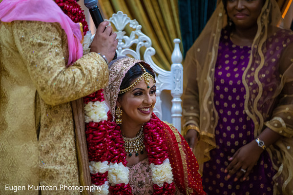 Indian bride at her ceremony with jaimala red and white garland.