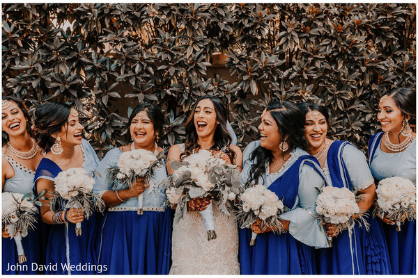 Indian bride with bridesmaids holding their bouquets.