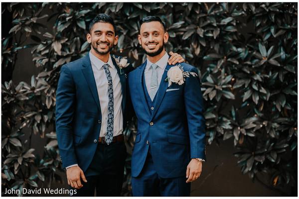 Indian groom posing with groomsmen in blue tuxedos.