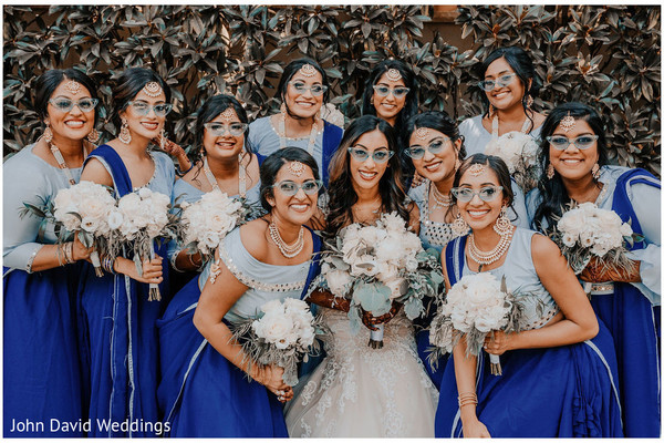 Indian bride with bridesmaids holding white bouquets.
