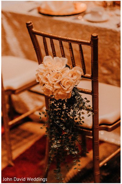 Indian wedding reception chair ivory roses decoration.