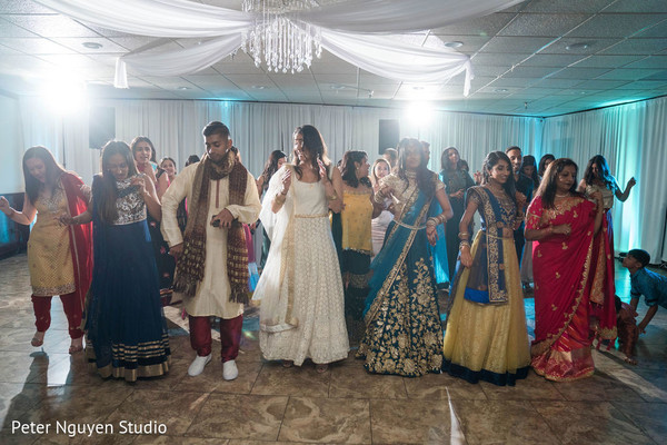 Indian bride dancing with guests at reception
