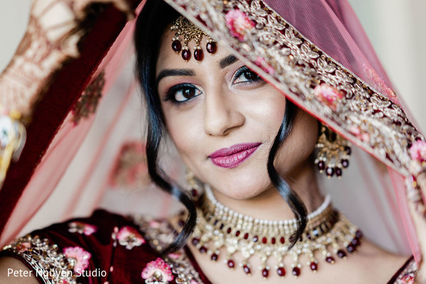 Indian bride with her pink ghoonghat over her head.