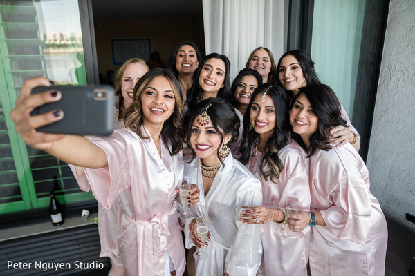 Indian bride with bridesmaids getting a selfie.