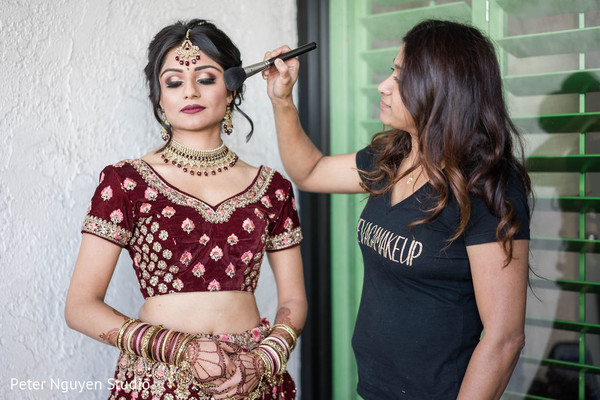 Indian bride getting her makeup on.