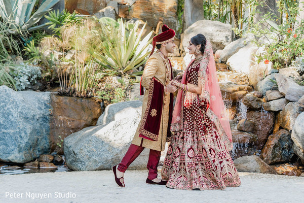 Indian bride and groom holding hands outdoors.