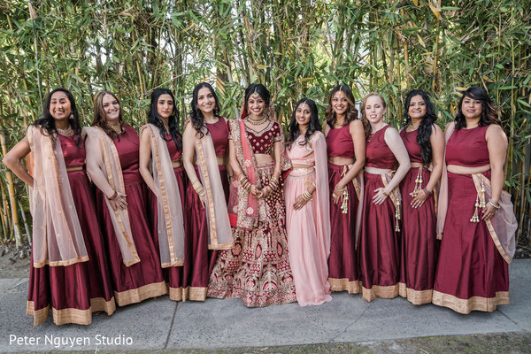 Indian bride posing with bridesmaids outdoors.