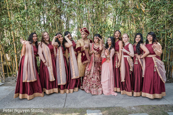 Indian couple posing with bridesmaids with their ceremony outfits.