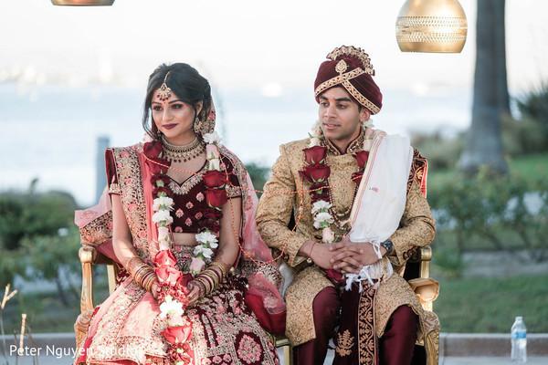 Indian couple seating at wedding mandap.