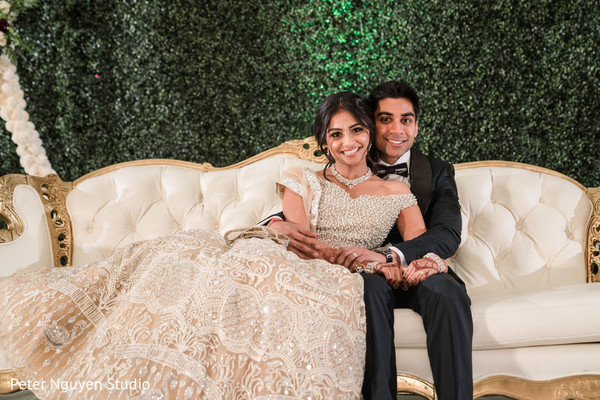 Indian couple's capture setaing on a ivory sofa.
