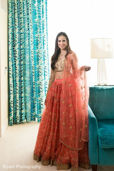 Indian bride on her coral and golden colored lehenga.