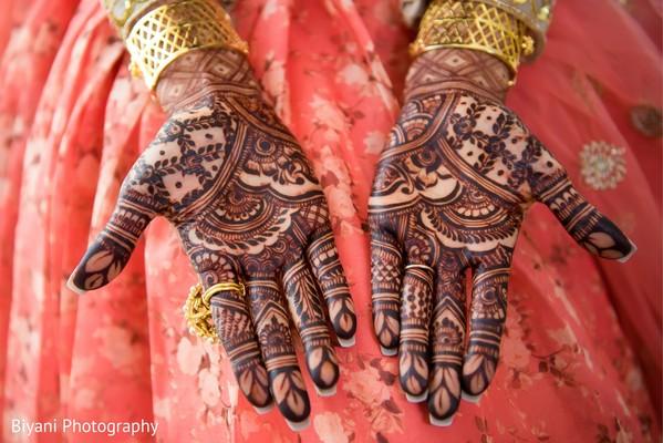 Indian bride showing her hands mehndi art.