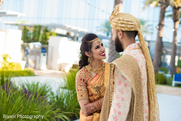Indian bride on her yellow red saree looking at groom.
