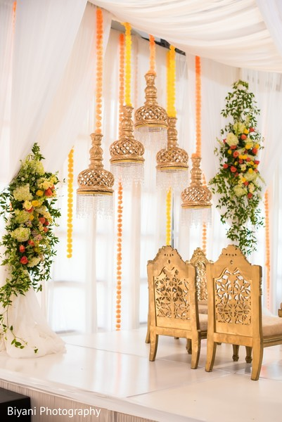 Mandap golden lamps yellow and orrange flowers decorations.