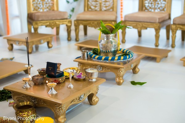 Indian wedding ceremony mandap golden tables.