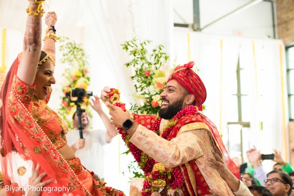 Indian groom putting the garland to bride ritual.