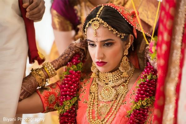 Indian bride with magenta flowers garland.