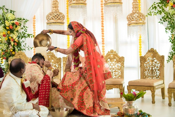 Indian bride pouring rice into grooms head.
