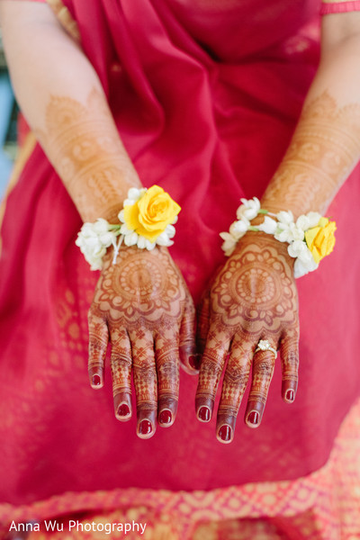Indian bride showing her red nail polish and her mehndi art.