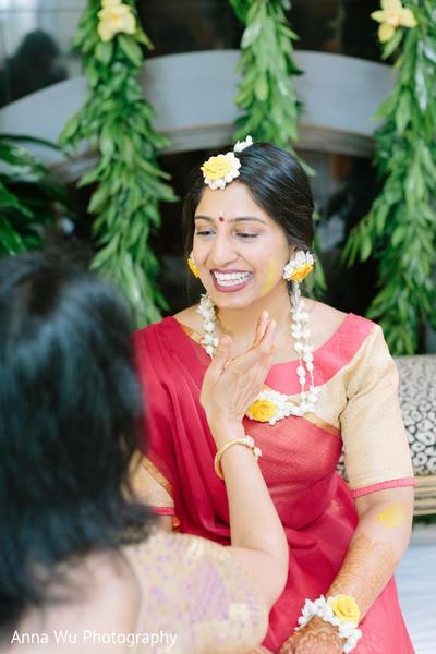 Maharani getting yellow turmeric paste on her face.