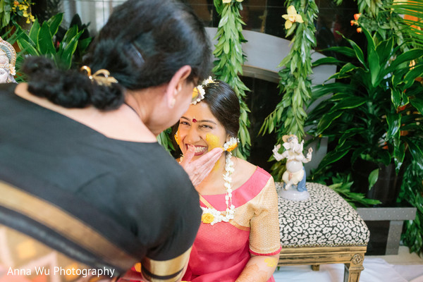 Indian bride getting yellow paste all over.