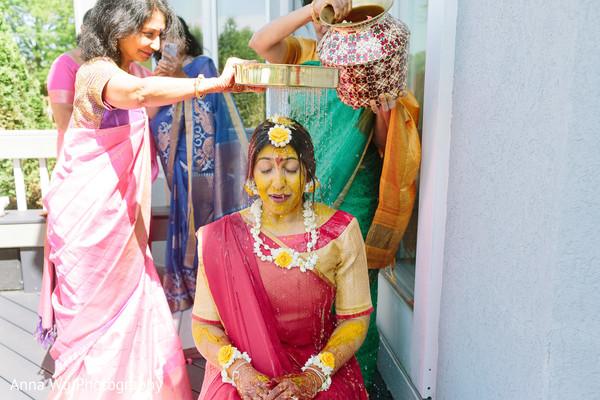 Indian bride getting showered at haldi.