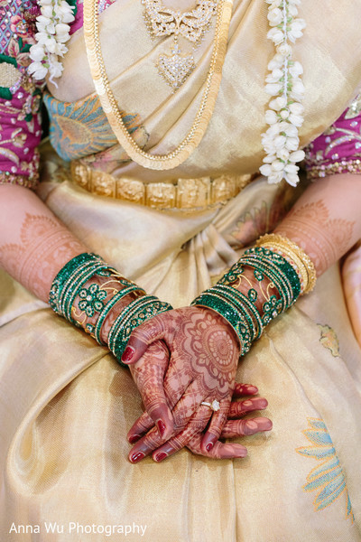 Indian bride wearing her golden and green chooras.