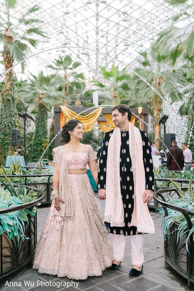 Indian couple in their light pink and black sangeet outfits.