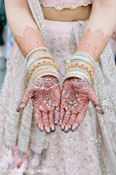 Indian bride showing her mehndi art and her diamond chooras.