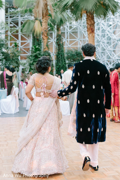 Indina couple walking on sangeet dancefloor.