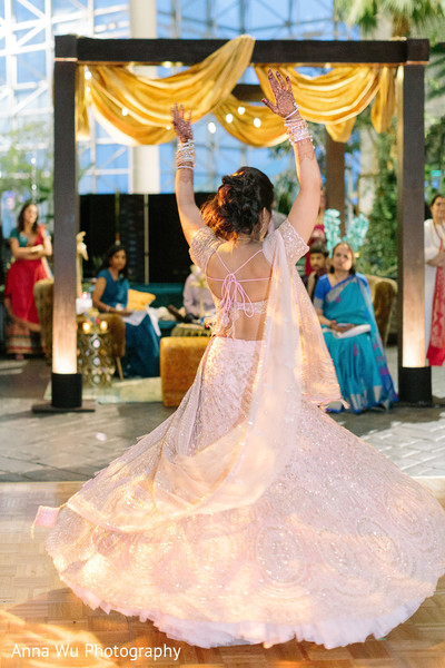 Indina bride dancing in her pink lehenga at Sangeet.